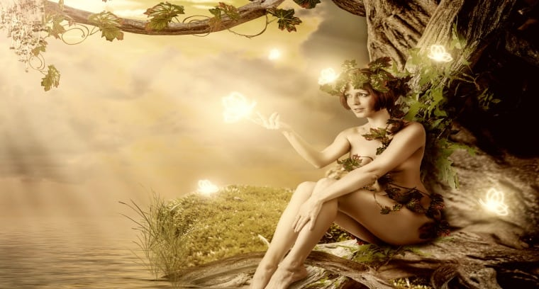 Fantasy fairytale beautiful woman - wood nymph or dryad sitting about water and big old tree