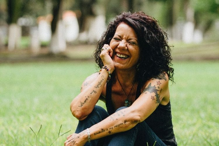 laughing woman sitting on grass-life over 50 blog