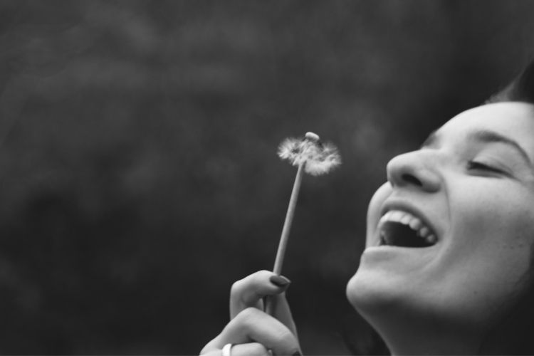 woman blowing a weed-how to keep a positive attitude