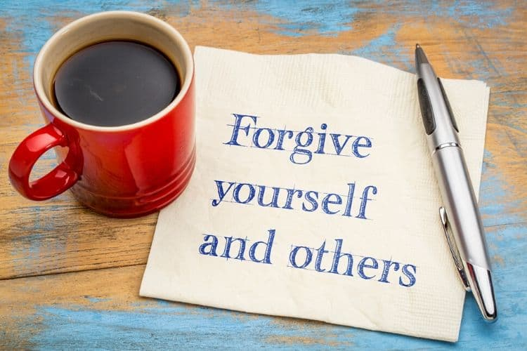 coffee mug and paper that says forgive yourself and others