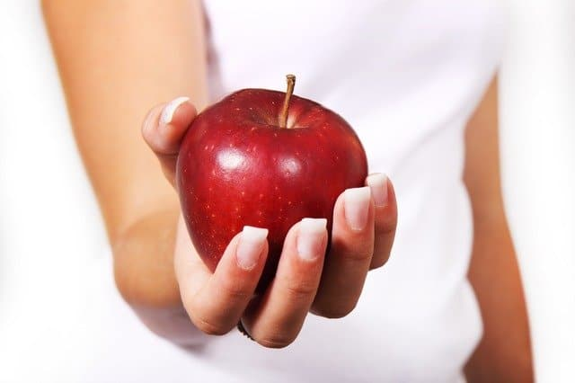 hand holding an apple-living a healthy lifestyle