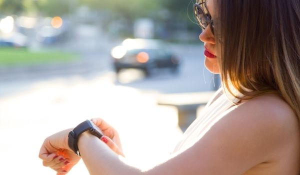 woman checking her watch-signs of disrespect in a relationship