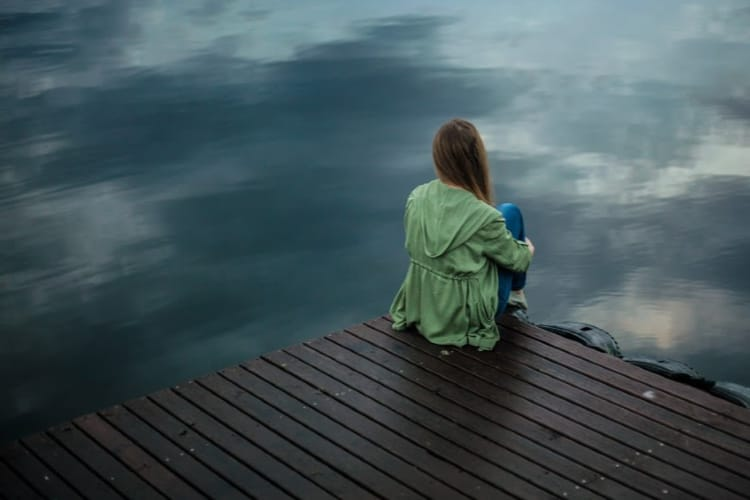 woman sitting on dock-ways to combat stress