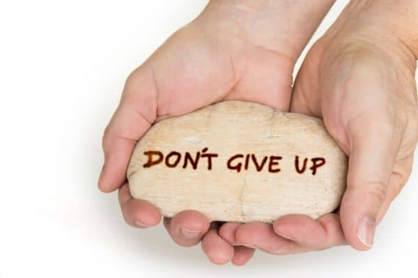 hand holding rock that says don't give up-finding an online therapist