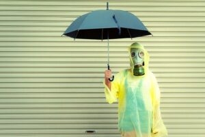 person with umbrella and gas mask