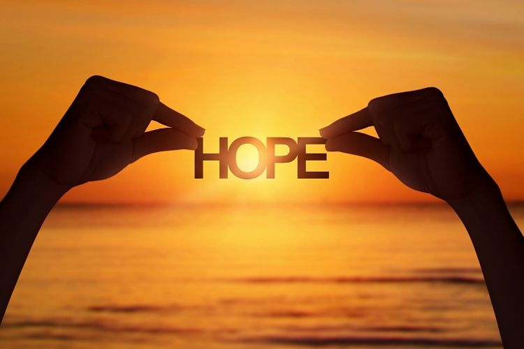 two hands holding the word hope-going through tough times blog post