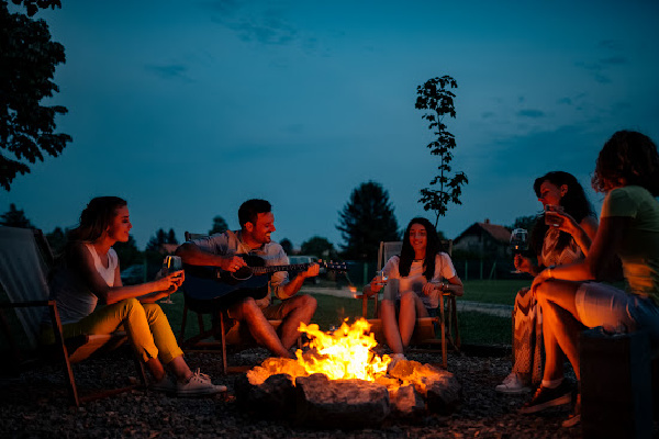 group of friends around a campfire prioritizing relationships